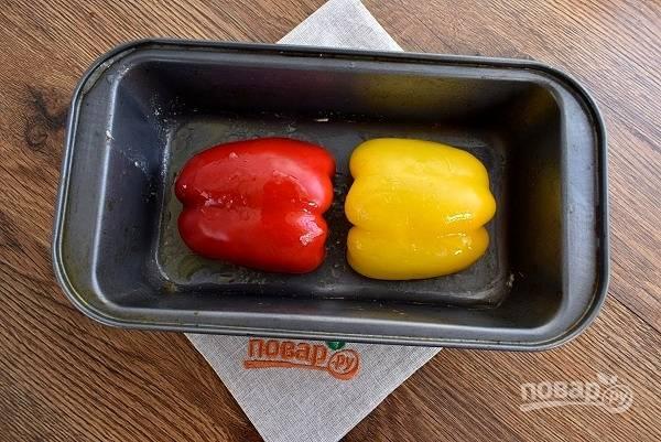 Перец разрежьте пополам, удалите плодоножки и семена. Поместите половинки перца срезом вниз в огнеупорную форму. Полейте 1 ст. л. оливкового масла. Запекайте в разогретой  духовке в течение 15 минут.