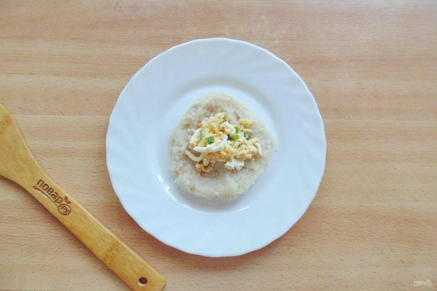 Порцию рыбного фарша в виде лепешки выложите на тарелку. На середину добавьте начинку из яйца, зеленого лука и сыра.
