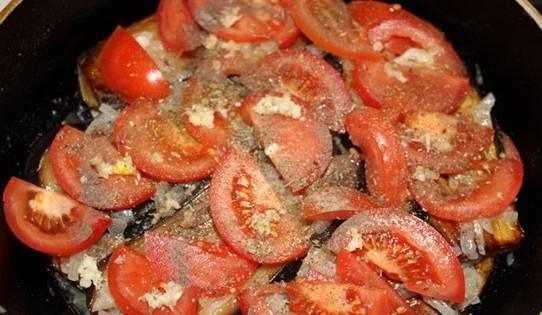 Теперь слоями выкладываем в сотейник сначала нарезанные тонкими ломтиками помидоры, затем пластинки баклажанов и обжаренный лук, повторяем слои еще раз и в завершение выкладываем последний помидоров. Каждый слой необходимо немного посолить и поперчить, посыпать измельченным чесноком и зеленью, по вкусу добавить лимонную кислоту. Накрываем сотейник крышкой и тушим все на медленном огне в течение 20 минут.
