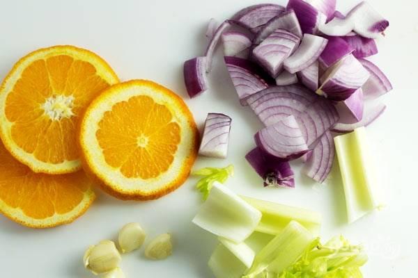 4. Тем временем вымойте и нарежьте ломтиками апельсин, измельчите лук, чеснок и сельдерей.