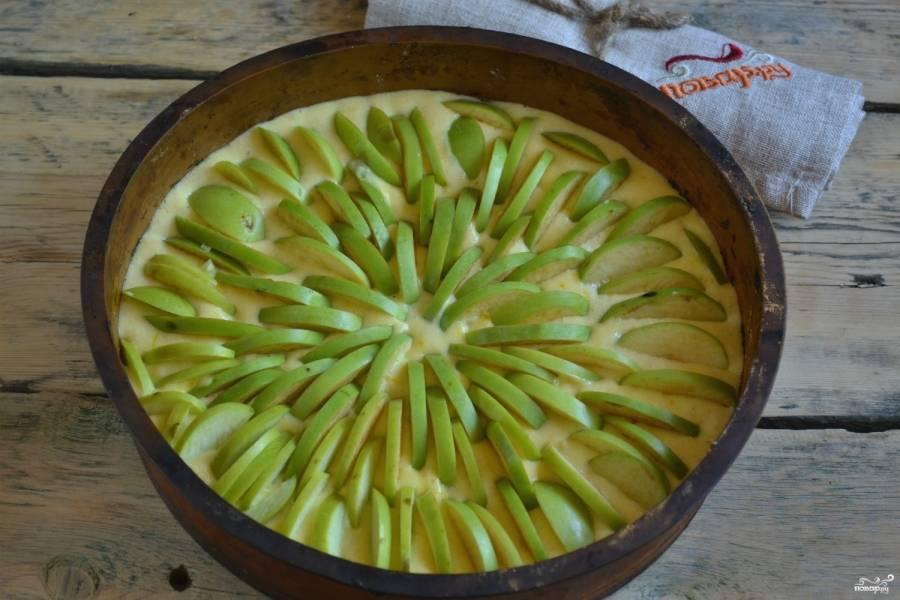 Вылейте тесто в форму для запекания, вставьте в него дольки яблок, как показано на фото.