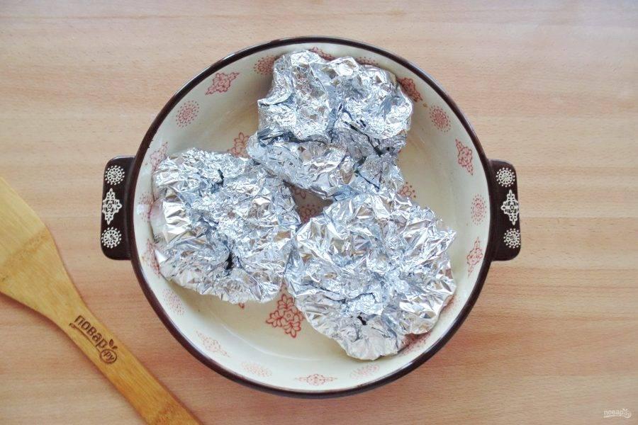 Плотно заверните в фольгу судака с овощами и выложите в форму для запекания.