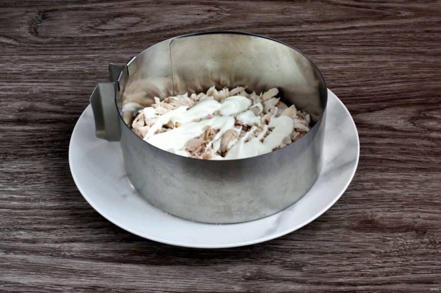 В сервировочное кольцо или просто на тарелку выложите слой куриного мяса и слегка смажьте его майонезом.