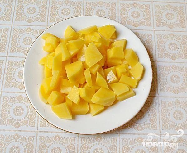 2. Чистим картофель и также нарезаем кубиками. Нарезанный картофель добавляем в кастрюлю, где варятся морковь и лук.