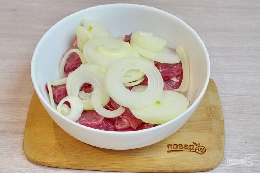 К нарезанному мясу добавляем нарезанный кольцами репчатый лук.