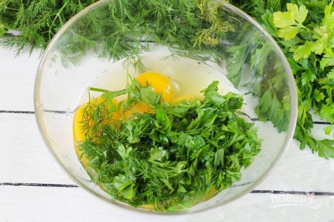 В емкость разбейте яйца, добавьте соль по вкусу и измельченную зелень. Все хорошо взбейте вилкой до однородности.