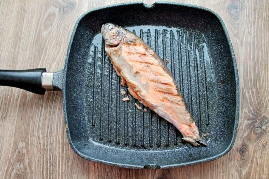 Нагрейте сковороду гриль и смажьте ее растительным маслом. Обжарьте на ней форель по одной минуте с каждой стороны. Переложите на тарелку.