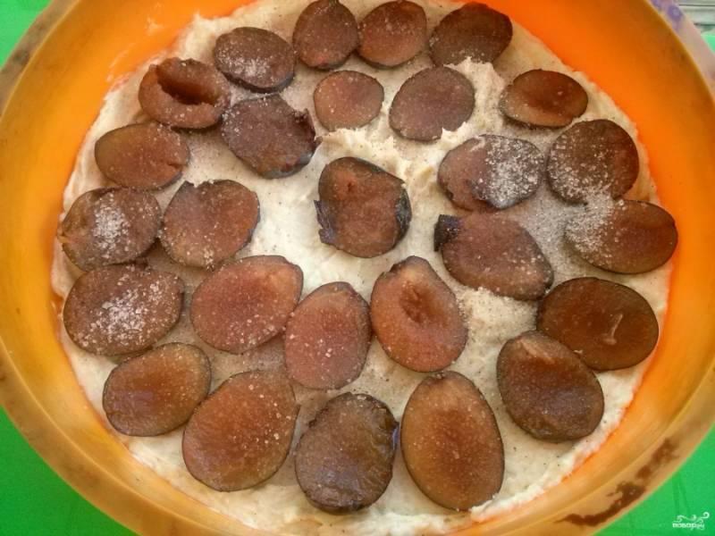 Сливы разрежьте на половинки и выложите на тесто, не вдавливая их внутрь. Сверху присыпьте коричным сахаром.