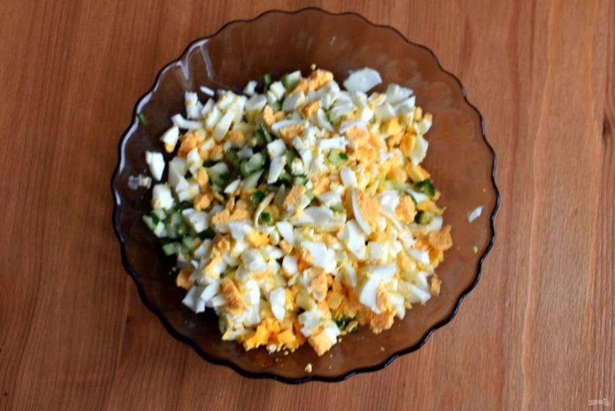 Отварите яйца вкрутую, остудите и очистите. Нарежьте яйца мелкими кубиками. Так же нарежьте свежий огурец. Добавьте нарезанные мелкими кубиками сыр и вяленые в масле помидоры.  Заправьте салат зерновой горчицей и лимонным соком, поперчите по вкусу и перемешайте.