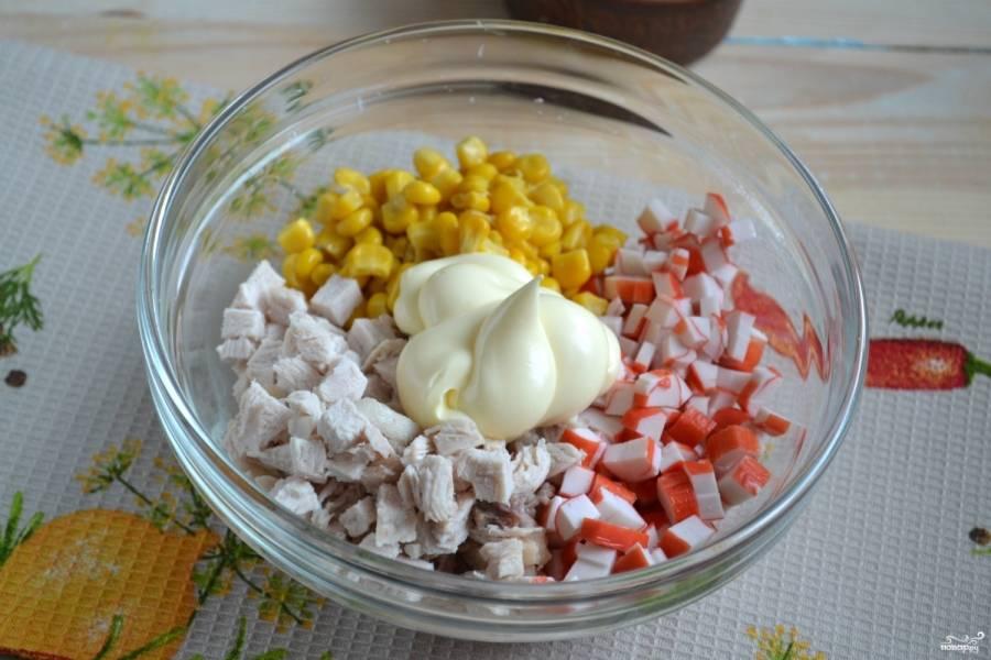 Смешайте измельченные крабовые палочки, куриное филе и кукурузу, заправьте майонезом.