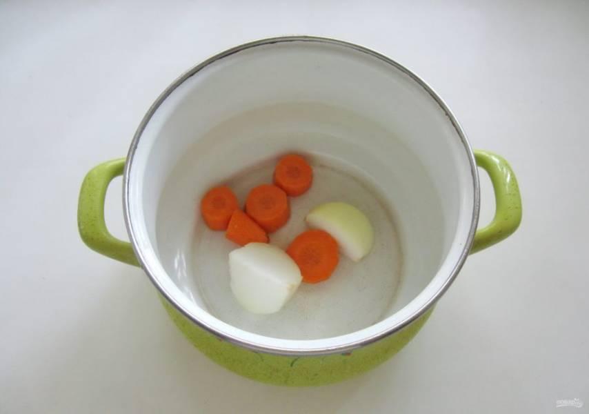 В кастрюлю выложите очищенный лук и морковь.