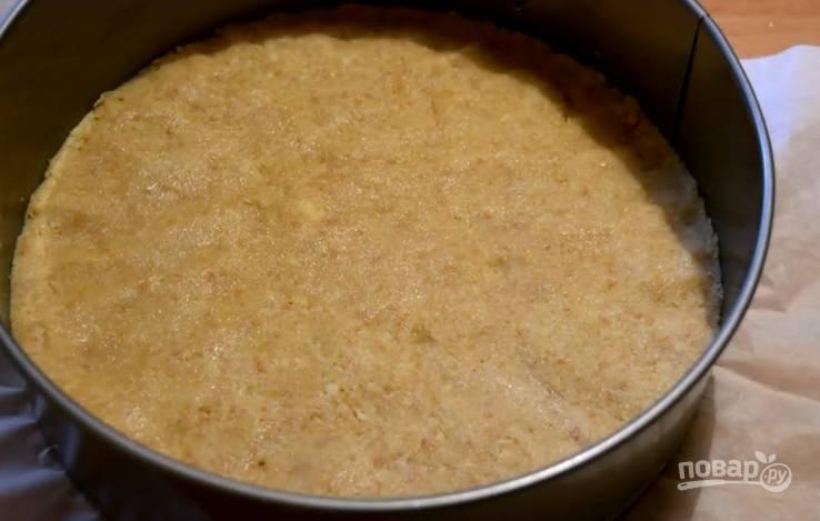 3. Форму для выпечки застелите пергаментом. Выложите печенье, утрамбуйте его плотно пальцами, чтобы получилась основа для чизкейка. Поставьте на время в холодильник.