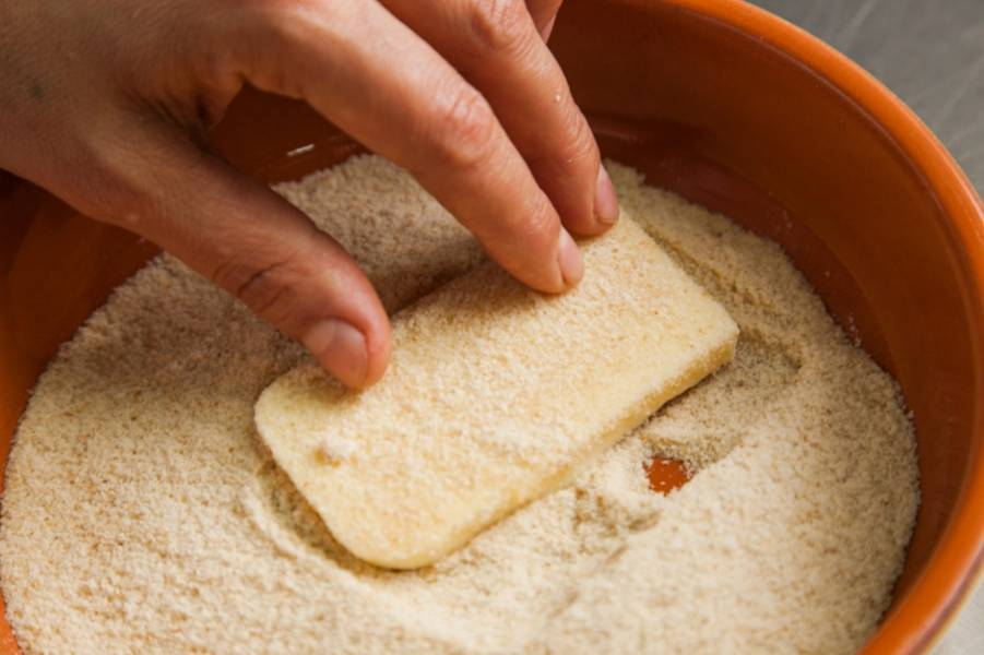 Панировочные сухари насыпьте в широкую тарелку. Если у вас нет готовых, то просто подсушите хлеб в духовом шкафу или тостере, чтоб получились сухарики. Затем измельчите хлеб в блендере. Окуните кусочки брынзы в панировочные сухари, обваляйте с обеих сторон.