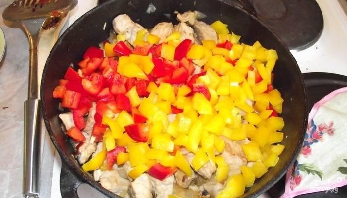 Когда лук станет мягким и пустит сок, выкладываем в казан нарезанный перец, перемешиваем.