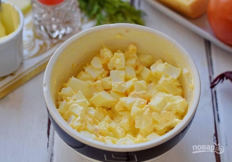 Вареные яйца очищаем и нарезаем кубиками. Смешиваем с майонезом и выкладываем поверх колбасы.