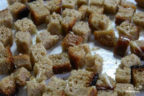 Хлеб нарежьте кубиками. Смешайте их с измельчённым чесноком и маслом в миске. Затем выпекайте в течение 10 минут при 180 градусах в духовке. Также можно обжарить на сковороде.