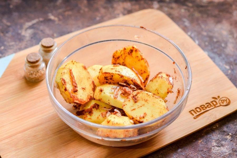 Хорошенько перемешайте все руками, чтобы каждый картофель был равномерно покрыт специями.