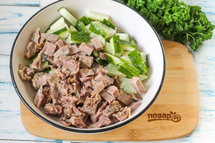 Следом нарежьте брусочками или кубиками остывший и очищенный отварной свиной язык, добавляя нарезку к остальным ингредиентам.