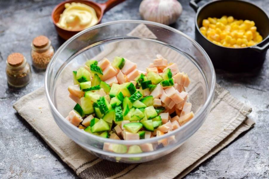 Следом сполосните и просушите свежий огурец, нарежьте его кубиками небольшого размера, переложите в салат.
