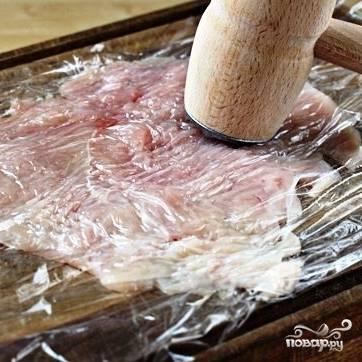 Кусочки куриного филе нужно положить между двух полиэтиленовых пленок и хорошенько отбить. Курица должна стать очень тонкой. Но не перестарайтесь и не порвите мясо :)