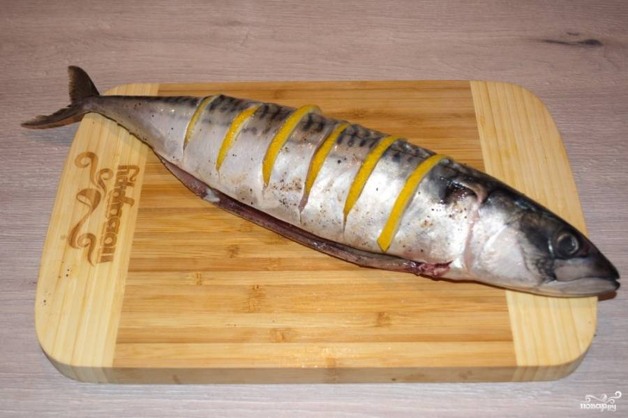 Продолжаем работать с рыбой. Пока начинка остывает, на тушке сделайте надрезы с обеих сторон. В надрезы вставьте дольки лимона.