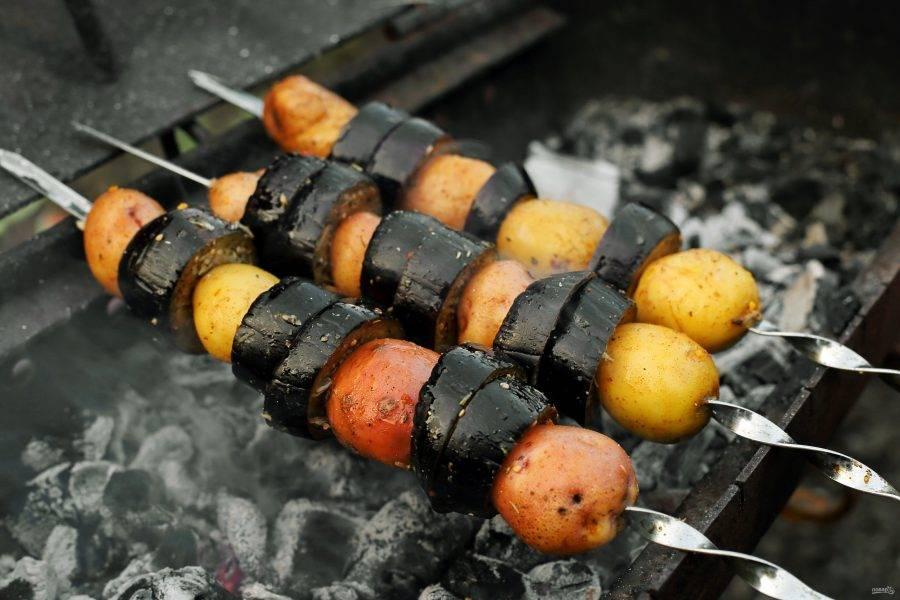 Нанизайте баклажан на шампур и готовьте периодически переворачивая на горячих углях около 15 минут. Я решила приготовить вместе с баклажанами и молодую картошку. Помимо других овощей, можно чередовать кружочки баклажанов с беконом, салом, грудинкой и т.д.