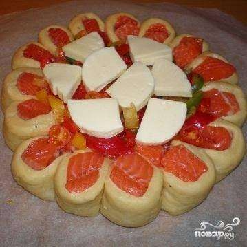 5.У нас осталась еще рыба. Нарезать ее мелко. Помидоры и перец нарезать кружочками. Сыр нарезать ломтиками. В середину пирога положить рыбу, сверху уложить помидоры и сыр и накрыть ломтиками сыра. Выпекается пирог около 30 минут при температуре 180 градусов.