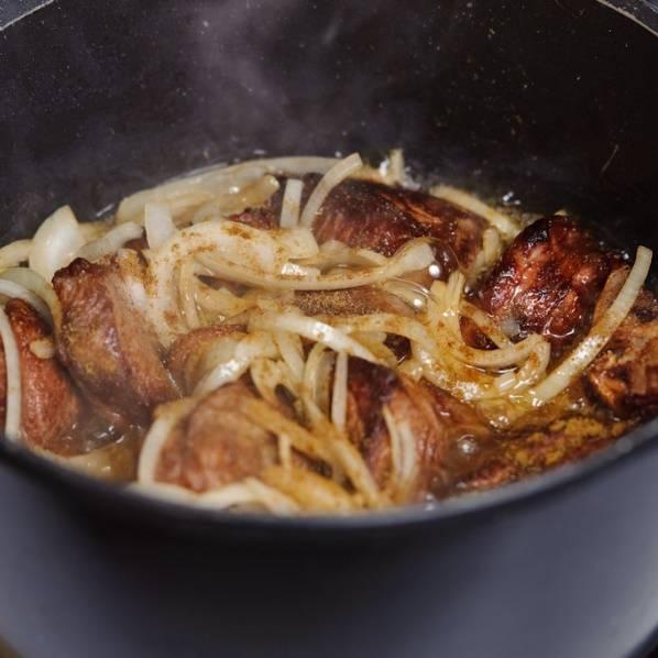 Опустить мясо в масло на дно чугунка. Обжаривать до появления коричневой корочки. Затем, добавить лук, щепотку тмина, 1/2 соли и черного молотого перца. Все хорошо перемешать.