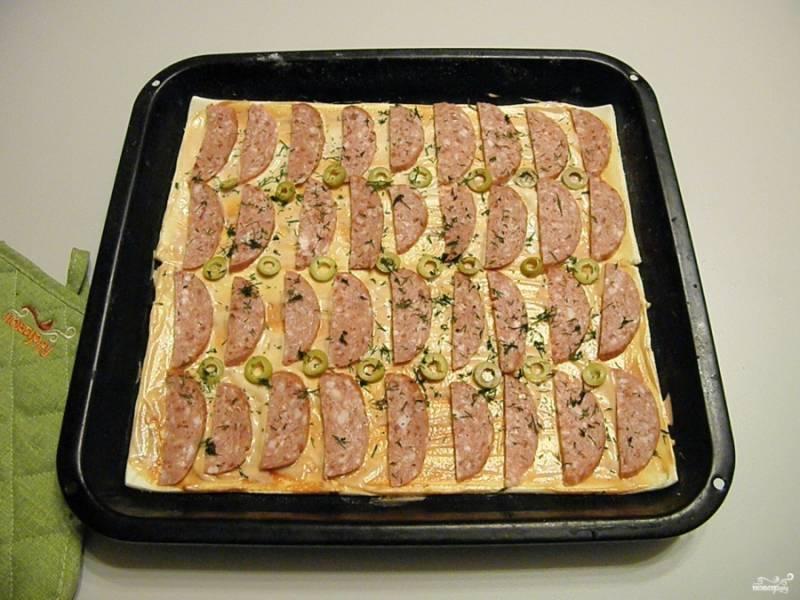 Разложите равномерно колбасу и оливки. Если есть красный сладкий перчик будет очень хорошо, добавьте. Притрусите рубленной зеленью для аромата.