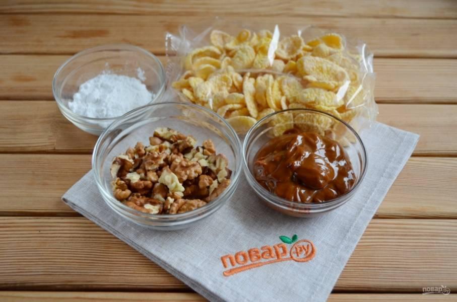Приготовьте уже готовые продукты: орехи, сгущенку вареную и кукурузные хлопья. Сахарная пудра понадобится в самом конце для украшения шишек.