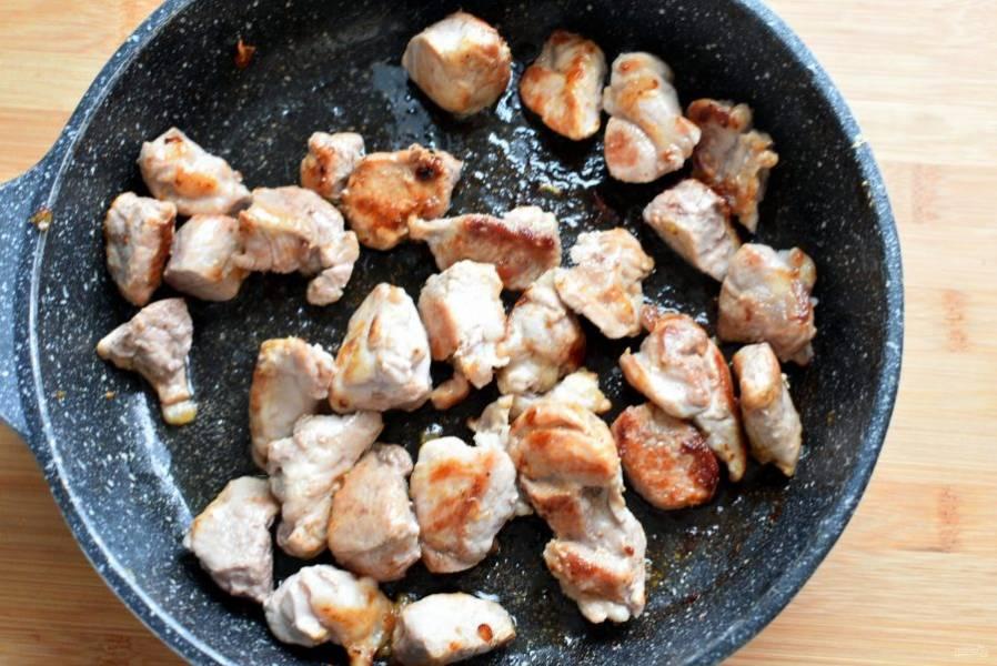 Переложите грудинку с овощами в жаровню для тушения в духовке. На оставшемся жире обжарьте свинину, нарезанную кубиками среднего размера, до румяной корочки.