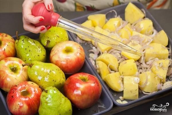 6. Очистите лук и нарежьте полукольцами. Картофель измельчите кубиками. Выложите на противень, сбрызните растительным маслом, посолите и присыпьте специями по вкусу. На отдельном противне разместите яблоки с грушами, также смазанные маслом и приправленные.