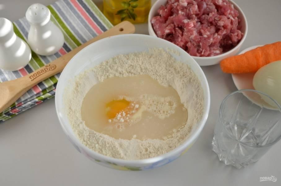 Сначала нужно сделать тесто. Для этого всыпьте два стакана муки в миску, вбейте яйцо, добавьте соль и воду. Начните замес теста, в процессе влейте 1-2 ст.л. масла для пластичности теста.