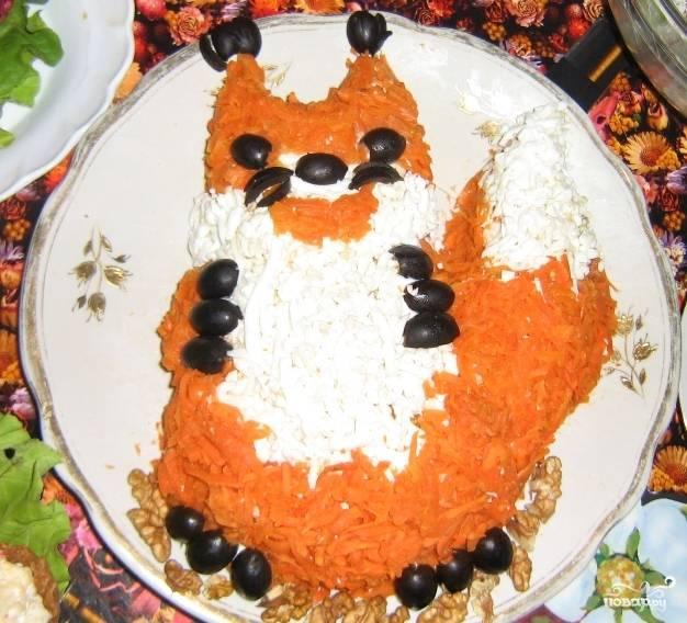 Натрите на крупной тёрке варёную морковь, и посыпьте ею салат, как шубку белочки. Лапки и мордочка белочки - из маслин.