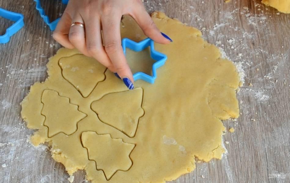 Тесто разделите пополам. Одну часть отправьте назад в холодильник, а вторую раскатайте толщиной 6-7 мм. С помощью специальных формочек выдавите печенюшки. То же проделайте со второй частью теста.