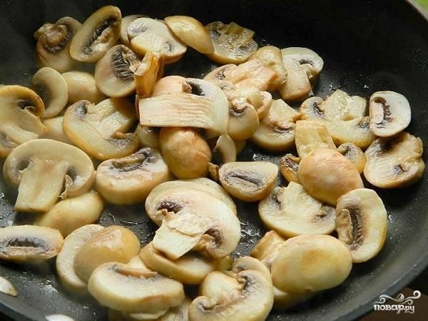 2. Выложите грибы на сковороду, обжарьте их минут 5, периодически помешивая. Тем временем очистите лук, нарежьте его мелкими кубами, измельчите чеснок.