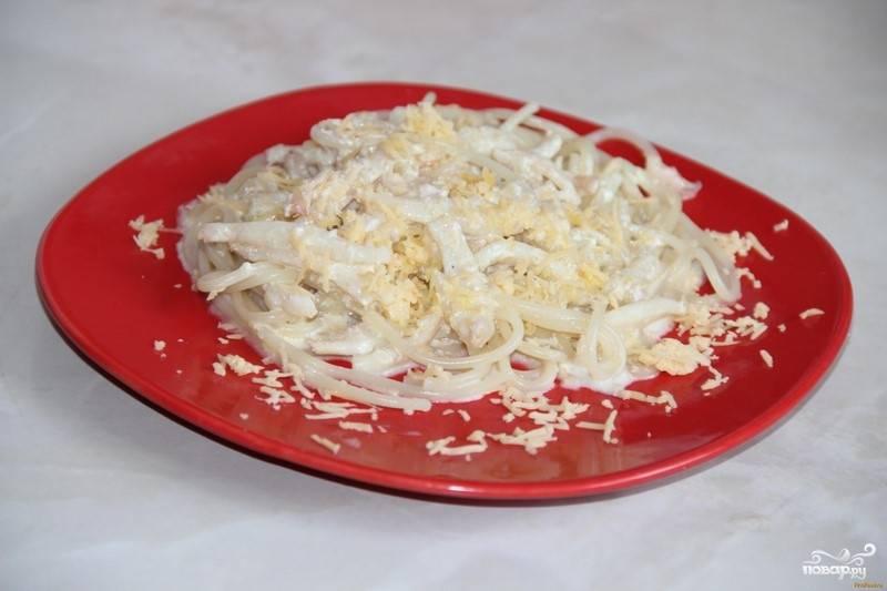 Отваренную пасту выложите в тарелки. Сверху выложите кальмара и налейте сливочный соус. Сыр натрите на крупной тёрке и посыпьте на горячую пасту с соусом.