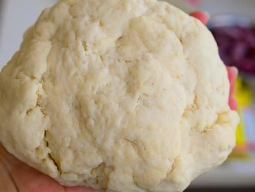 2. В глубокую мисочку отправьте творог с сахаром и щепоткой соли. Вымешайте все до однородности, добавьте молоко и растительное масло. Постепенно всыпайте просеянную муку с разрыхлителем и замешивайте мягкое, эластичное тесто. Оно не должно липнуть к рукам, но при этом не делайте его слишком плотным.