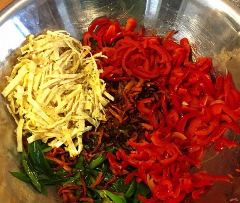 3.Вымойте зеленый лук и нарежьте его перьями, обжарьте их на раскаленной сковороде 30-60 секунд, затем переложите в тарелку. Перец нарежьте полукольцами и обжарьте на сковороде 2-3 минуты. Переложите в большую миску яичные полоски, обжаренные овощи и мясо.