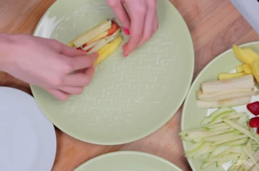 2. Рисовую бумагу смочите в холодной воде с обеих сторон и выложите на нее начинку: сначала нарезанные ломтиками киви и клубнику, затем остальные фрукты.