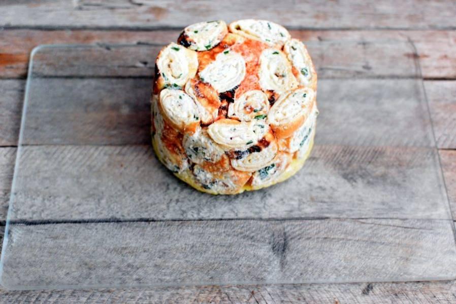 Охлажденный салат аккуратно выложите на блюдо, потянув за концы пленки.