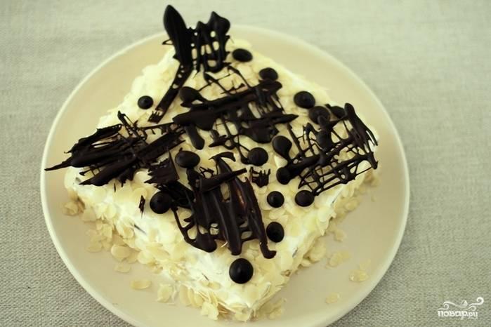 На пергамент нанесите растопленный шоколад в виде узоров, дайте им застыть в холодильнике.  А потом ими можете украсить готовый творожный торт из печенья.