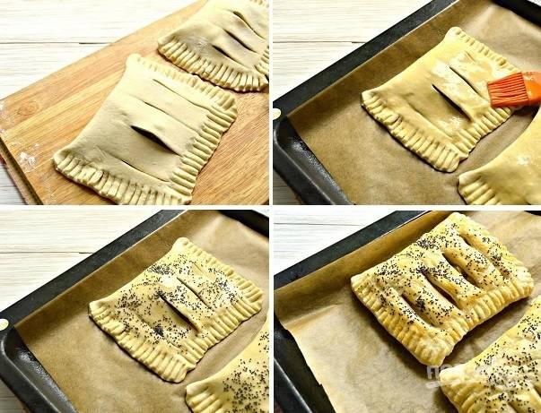 5. Аккуратно сверните слойку и залепите края. Выложите на противень, застеленный пергаментом. Яйцо взбейте в небольшой мисочке, смажьте слойки с помощью кисточки. Присыпьте щепоткой мака и отправьте в разогретую до 180 градусов духовку минут на 20.