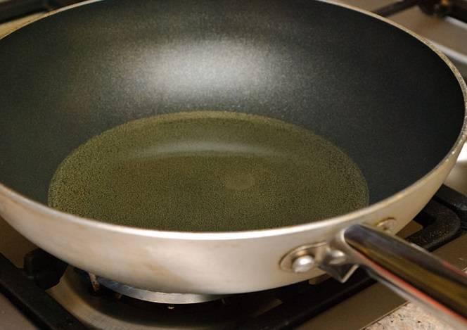 3. В глубокую сковороду влейте масло. Оно должно заполнять сковороду на 2,5 см от дна. Хорошенько разогрейте на большом огне. Нужную температуру можно проверить двумя способами. Вкиньте маленький кусочек хлеба, он должен стать золотисто-коричневым через 10 секунд. Либо вставьте деревянную ложку, должны пойти пузырьки.
