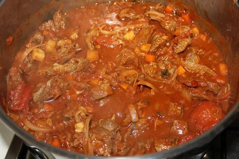 Уменьшаем огонь до среднего и тушим овощи с мясом без крышки в течение 20 минут, жидкость в кастрюле должна умеренно кипеть.