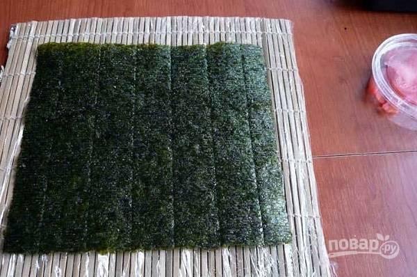 1. Первым делом отварите рис для суши, добавьте обязательно уксус. Выложите лист нори на коврик.