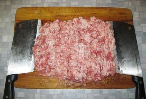 Продолжаем готовить начинку. Как только говядина была нарублена в фарш, пришла пора свинины. Ее особо обрезать не нужно, поскольку там в основном не пленки, а сало, но, разумеется, если что-то вас во внешнем виде не устраивает - лучше это срезать и отправить в бульон. По моему убеждению, наличие сала в пельменях - вещь очень важная, поскольку именно сало делает начинку блюда мягче, нежнее и сочнее. Итак, рубим свинину в фарш. Если в процессе рубки топориком жирные куски свинины начинают прилипать к топорику, то просто погрейте топорики несколько секунд под струей горячей воды из-под крана.