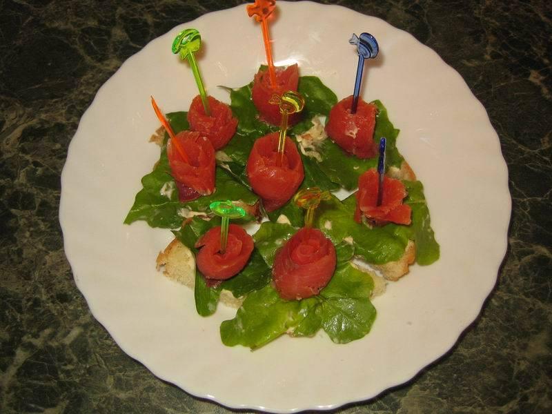 Рыбу порежьте на полоски, заверните в рулетики и выложите сверху на салат. Закрепите канапе шпажками.  Вот наши канапе из красной рыбы и готовы. Приятного аппетита!