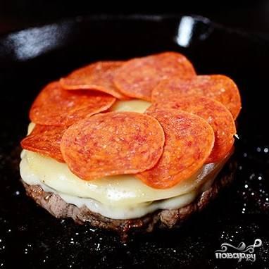 Теперь действуем быстро. Не снимая сковороду с огня, кладем на практически готовую котлету ломтик сыра (моцарелла или проволоне) и немного колбасы пепперони.