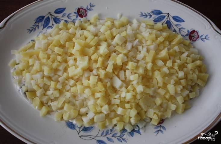 Отварной картофель нарезаем мелкими кубиками и выкладываем следующим слоем.